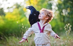 boy and crow, best friends, boy and his crow friend, the bird and the child against the backdrop of greenery, little boy in the summer park, sunny forest, ecology, nature, clean air, freedom