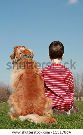 Boy and Dog Sitting on a Hill