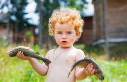 boy and fish, kid holds in a hand raw fresh fish on a background wild nature and deer that eats a grass, baby and trout
