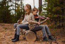 Boy and girl, brother and sister, teenagers play the trumpet and violin sitting in the woods on a log.