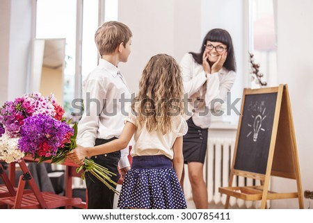 Boy and girl children give flowers as a school teacher in teacher\'s day. The day of knowledge, education, appreciation, generation.