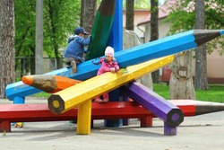 Boy and girl climbing giant colorful wooden pencils on the children playground in the city park