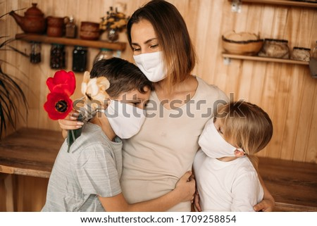 Boy and girl congratulate mom on Mother's Day. Masked quarantined family on mother's day.