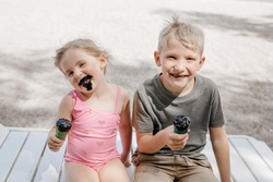 Boy and girl dirty because of black ice cream. The grimy faces of children. Brother and sister eat unusual ice cream on the beach. High quality photo