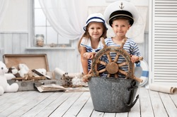 Boy and girl dressed as a captain and sailors played on the ship out of the bath in his room