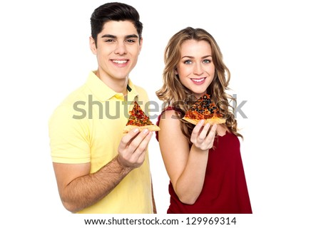 Boy and girl each holding slice of yummy pizza.