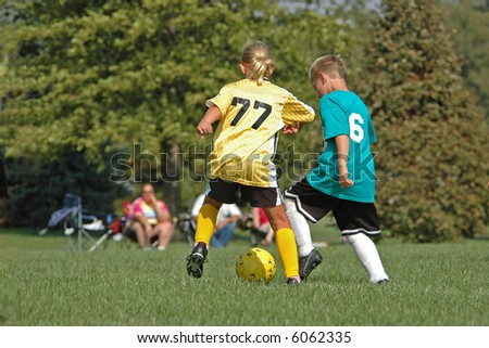 Boy and Girl Fight for Soccer Ball Foto stock ©