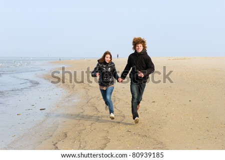 Boy and girl happy running at the Dutch beach