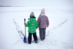 Boy and girl have fun and removing snow from the ice on the frozen lake in heart shape. Winter romantic, silence and wild nature, active winter weekend, outdoor activities, icy landscape, lifestyle