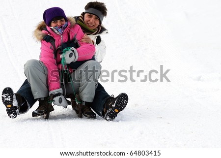 boy and girl having fun in the snow, sledging.