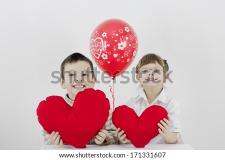 boy and girl hold heart in hands and smile,best focus glasses, teeth, boy, soft focus hand and a balloon
