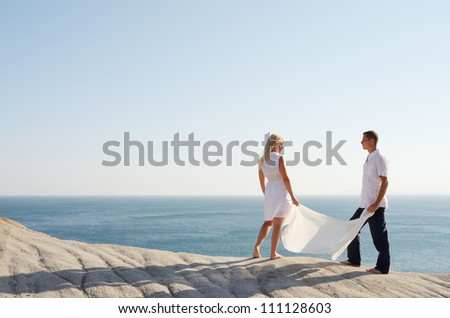 Boy and girl holding a white shawl standing on a rock and look at each other