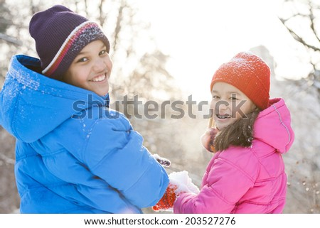 boy and girl holding snow in hands. brother and sister playing outside