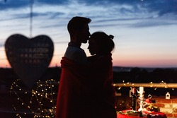 Boy and girl hug each other tender standing on the rooftop in the rays of evening lights and having a romantic dinner