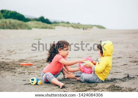 Boy and girl in a dispute over a toy at the beach, Wales, United Kingdom.
