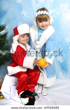 boy and girl in costume of Santa Claus and Snow Maiden about trees