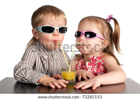 boy and girl in sunglasses drinking juice from glass