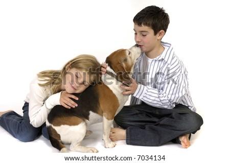 Boy and girl loving pet Beagle dog.