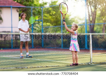 Boy and girl playing tennis on outdoor court. Kids with tennis racket and ball in sport club. Active exercise. Summer activities for children. Training for young kid. Child learning to play #770708404