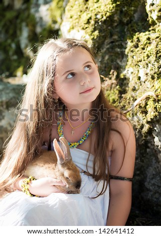 Boy and girl playing with pet rabbit. Girl walking in the park