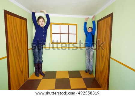 Boy and girl pose in room with optical illusion. #492558319