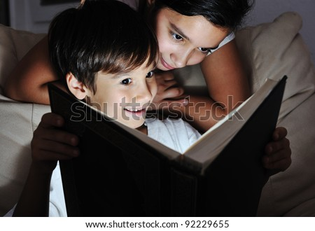 Boy and girl reading light book at night, children concept - stock photo