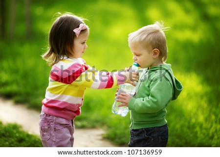 boy and girl sharing bottle of water