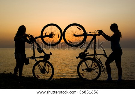 Boy and girl showing there bikes, and watching sunset on the sea.