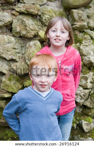 boy and girl siblings standing against an old stone wall