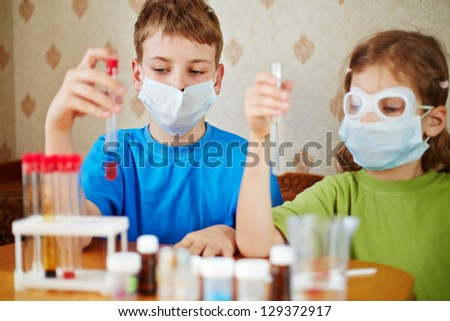 Boy and girl sit at table with chemical reagents and look at test tubes in their hands