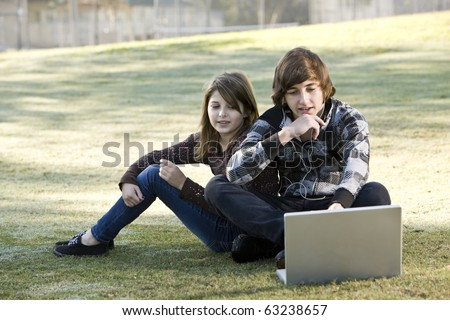 Boy and girl sitting on grass with laptop, online in park