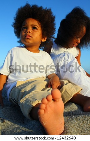 Boy and girl sitting on the sand