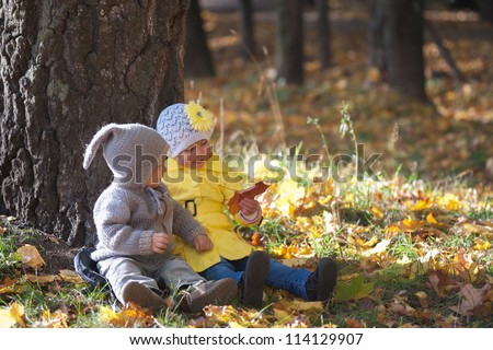 Boy and girl sitting under a tree in the autumn park