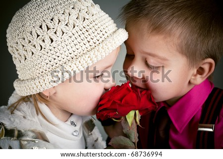 boy and girl sniffing a rose