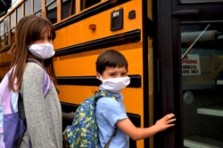 Boy and girl, students, children wearing face masks getting on school bus. For education, health, medical, environmental, and safety concepts regarding coronavirus, schools, reopening, and facemasks.