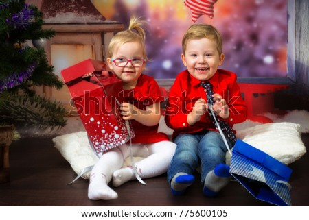 Boy and girl twins posing in christmas scenery