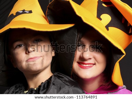 Boy and girl wearing halloween costume on black background