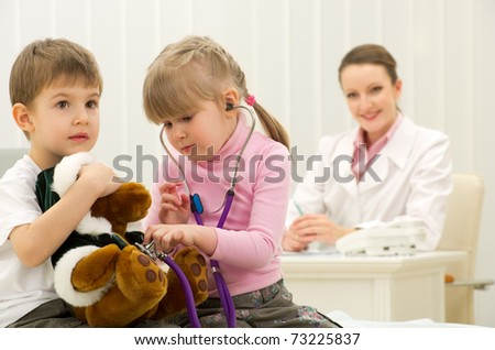 Boy and girl 4 years old playing doctor in a medical office