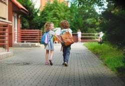 Boy and girlie go to school having joined hands. Warm September day. Good mood. Behind backs at children satchels. The girlie laughs. Back to school.  Little first grader.