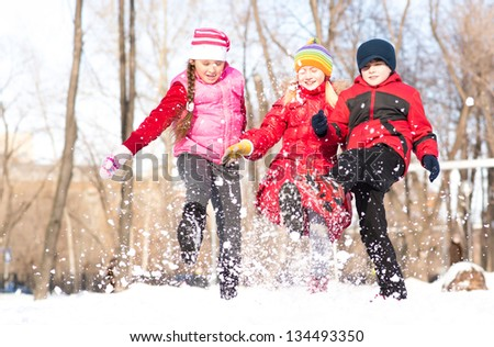 Boy and girls playing with snow in winter park, spending time together outdoors