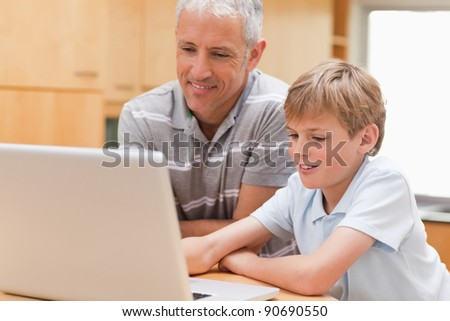 Boy and his father using a notebook in their kitchen