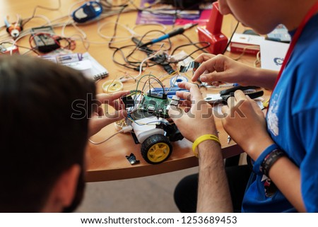 Boy and his mentor working on a self made computer controlled vehicle