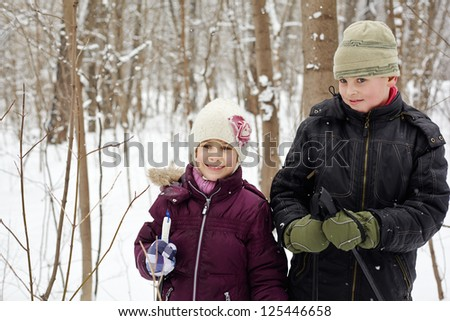 Boy and his younger sister stand in winter park with ski poles in their hands