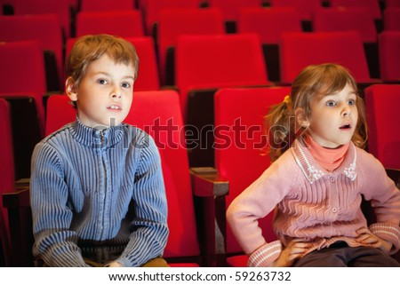 boy and  little girl sitting on armchairs at cinema, girl has opened mouth