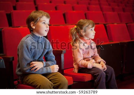 boy and  little girl sitting on armchairs at cinema, steadfastly looking