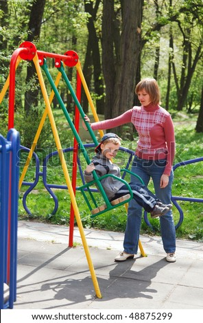 Boy and mother play with swing on may city park (pleasure-ground).