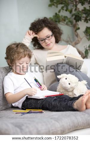 Boy and teenage girl relaxing on sofa