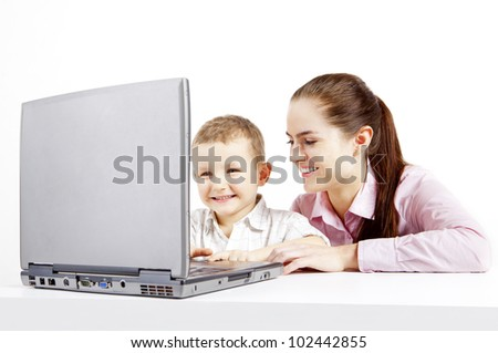 Boy and woman sit at the laptop. They are happy. Boy had satisfaction of work with laptop.