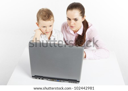 Boy and woman sit at the laptop. They are learning use the laptop.