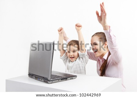 Boy and woman sitting by laptop. They are very happy. A new technology and child.
